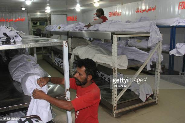 Pakistani volunteers adjust the dead bodies of heatwave victims at the Edhi Foundation morgue in Karachi on May 22 2018 Dozens of people are feared...