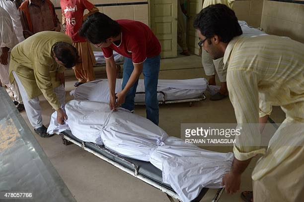 Pakistani volunteers and relatives prepare to shift the bodies of heatwave victims into the cold storage of the Edhi morgue in Karachi on June 22...