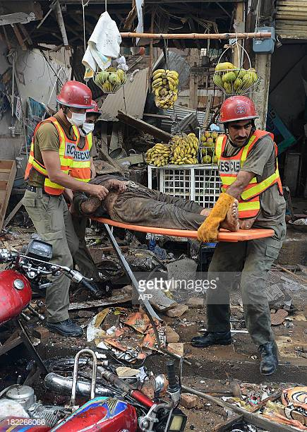 Pakistani volunteers carry a blast victim at the site of a bomb explosion in the busy Kissa Khwani market in Peshawar on September 29 2013 A bomb...