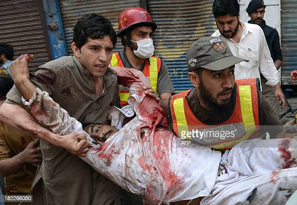 Pakistani volunteers carry an injured blast victim at the site of a bomb explosion in the busy Kissa Khwani market in Peshawar on September 29 2013 A...