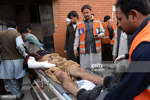 Pakistani volunteers carry an injured victim of a grenade attack at a cinema in Peshawar on February 11 2014 A triple grenade attack on a cinema...