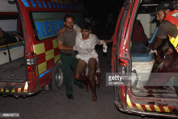 Pakistani volunteers help injured blast victims as they arrive at a hospital in Multan on September 13 2015 At least nine people were killed and 42...