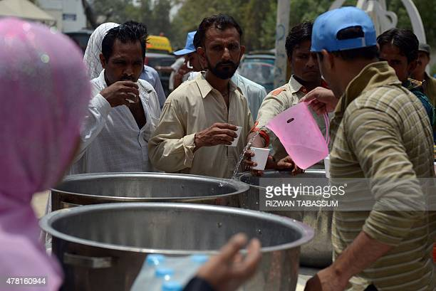 Pakistani volunteers provide drinking water to people outside a government hospital during a heatwave in Karachi on June 23 2015 More than 500 people...