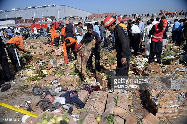 Pakistani volunteers search the site of a bomb explosion at the fruit and vegetable market in Islamabad on April 9 2014 A bomb explosion killed at...