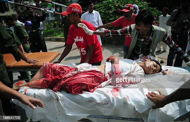 Pakistani volunteers shift an injured blast victim to a hospital following a bomb explosion in Karachi on May 11 2013 A Taliban bomb attack targeting...