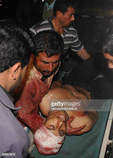 Pakistani volunteers shift the body of a suicide attack victim from a stretcher outside a hospital in Multan on February 5 2009 At least 21 people...