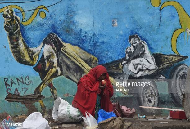 Pakistani waste picker eats an apple in front of a mural painting on a street in Lahore on February 17 2019