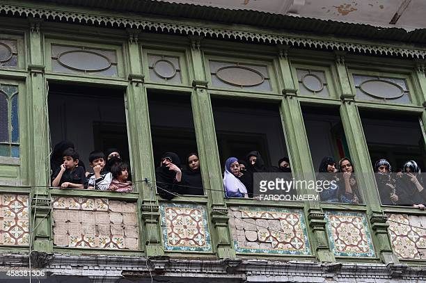 Pakistani watch a religious Ashura procession from the windows of their home in Rawalpindi on November 4 2014 Ashura mourns the death of Imam Hussein...