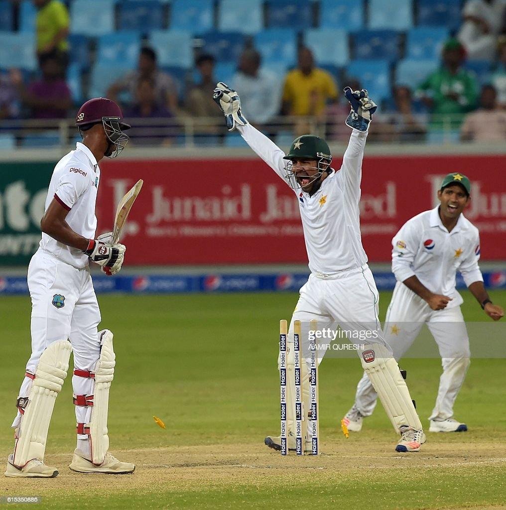Pakistani wicketkeeper Sarfraz Ahmed (C) and teammate Asad Shafiq (R) celebrate after they bowled out of West Indies batsman Roston Chase (L) on the final day of the first day-night Test between Pakistan and the West Indies at the Dubai International Cricket Stadium in the Gulf Emirate on October 17, 2016. / AFP / AAMIR