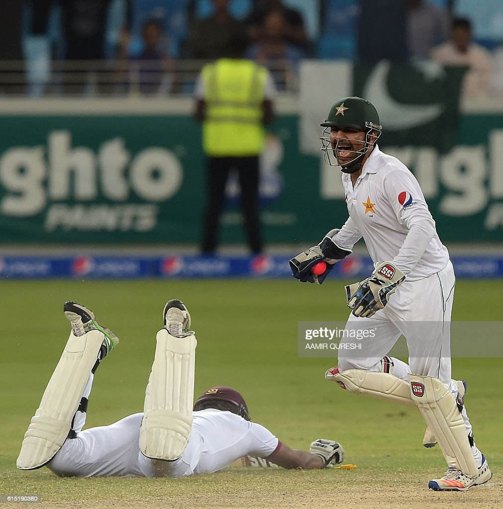 Pakistani wicketkeeper Sarfraz Ahmed (R) celebrates after successfully running out of West Indies' batsman Shannon Gabriel (L) on the final day of the first day-night Test between Pakistan and the West Indies at the Dubai International Cricket Stadium in the Gulf Emirate on October 17, 2016. Pakistan beat West Indies by 56 runs in the first day-night Test on the fifth and final day in Dubai on October 17, taking a 1-0 lead in the three-match series. / AFP / AAMIR