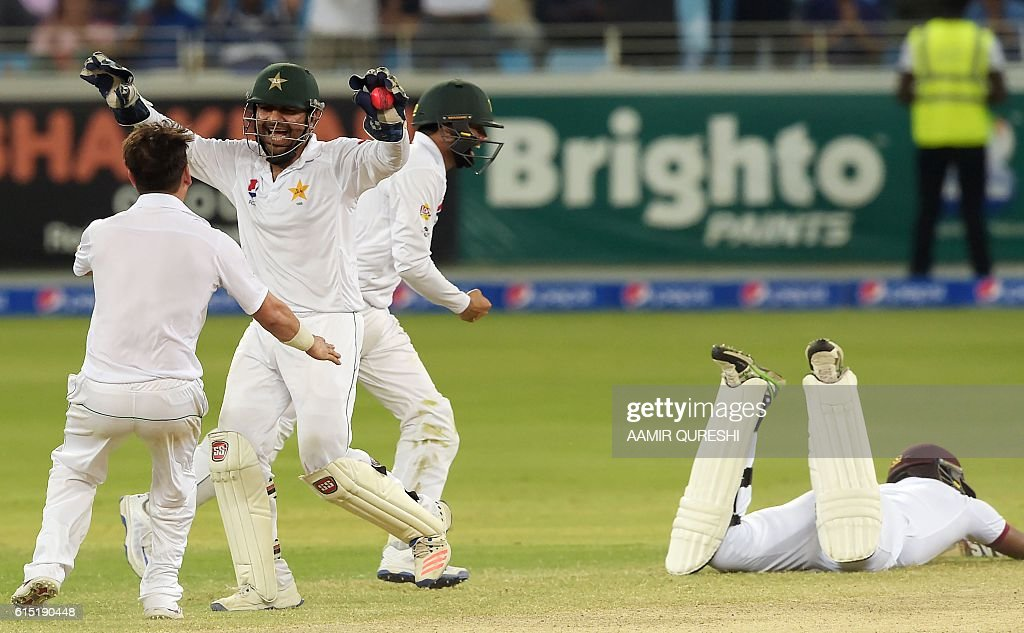 Pakistani wicketkeeper Sarfraz Ahmed (2L) celebrates with his teammate Yasir Shah (L) after he successfully ran out West Indies' batsman Shannon Gabriel (R) on the final day of the first day-night Test between Pakistan and the West Indies at the Dubai International Cricket Stadium in the Gulf Emirate on October 17, 2016 Pakistan beat West Indies by 56 runs in the first day-night Test on the fifth and final day in Dubai on October 17, taking a 1-0 lead in the three-match series. / AFP / AAMIR