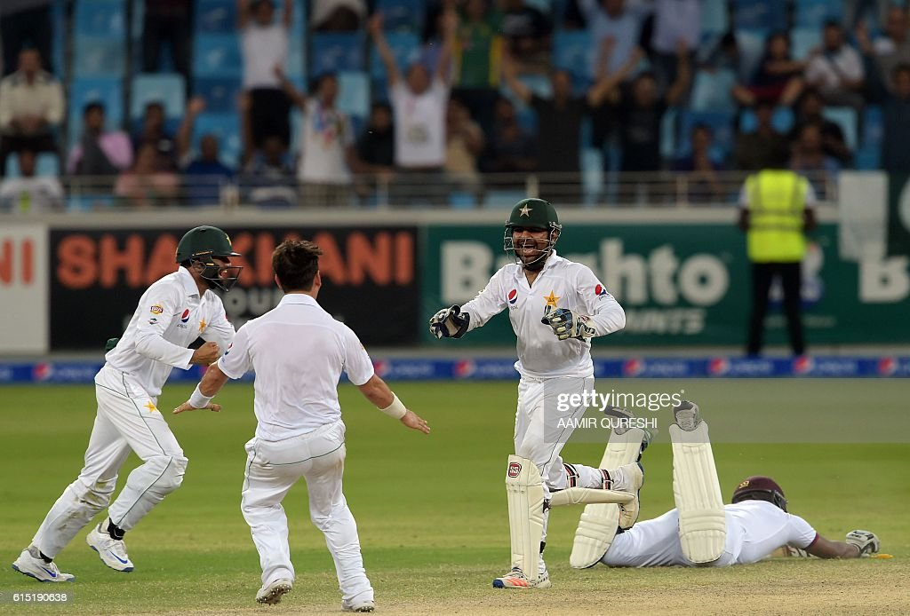 Pakistani wicketkeeper Sarfraz Ahmed (2R) celebrates with his teammate Yasir Shah (2L) after he succussfully ran out West Indies' batsman Shannon Gabriel (R) on the final day of the first day-night Test between Pakistan and the West Indies at the Dubai International Cricket Stadium in the Gulf Emirate on October 17, 2016. Pakistan beat West Indies by 56 runs in the first day-night Test on the fifth and final day in Dubai on October 17, taking a 1-0 lead in the three-match series. / AFP / AAMIR