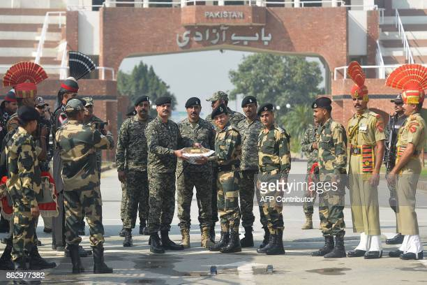 Pakistani Wing Commander Bilal presents sweets to Indian Border Security Force commandant Sudeep on the occasion of the Diwali festival at the...