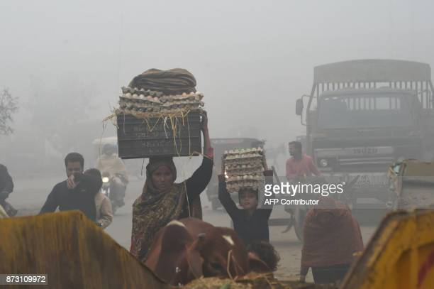 A Pakistani woman and child carry eggs on a street amid heavy smog in Lahore on November 12 2017 Large swathes of Pakistan and north India see a...