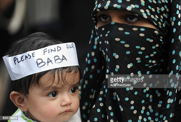 A Pakistani woman carries her baby during a protest of missing persons families in Karachi on December 7 2008 ahead of the Muslim festival of Eid...