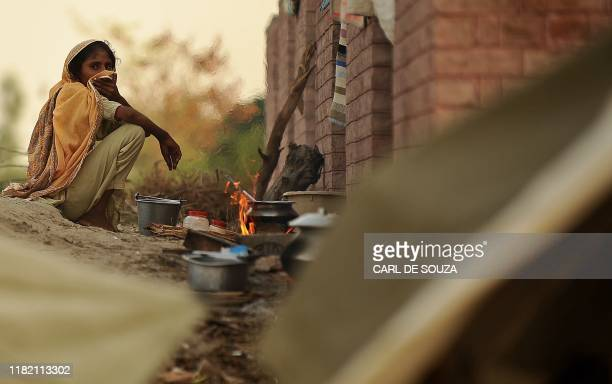 Pakistani woman displaced by flooding cooks at Motehin Camp organised by Qarshi Dawakhana NGO, in Sultan on September 6, 2010. The UN has warned that...