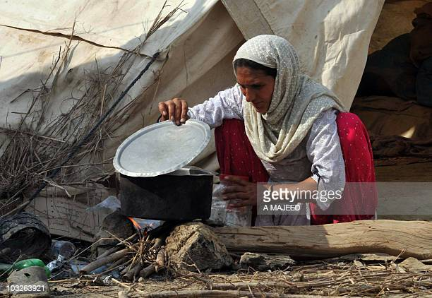 A Pakistani woman displaced by floods prepares food outside a makeshift tent in Charsada on August 5 2010 Pakistan began evacuating half a million...