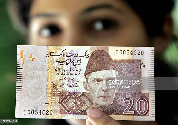 Pakistani woman displays a new 20 Rupees banknote in Islamabad 13 August 2005 The State Bank of Pakistan launched the banknote of 20 Rupees...