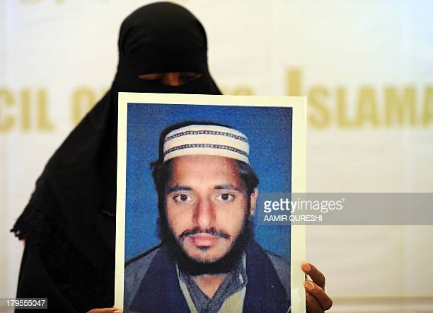 Pakistani woman Fatima shows a photograph of her husband Iftikhar Ahmed, who is under detention by the US at a prison in Afghanistan, during an...