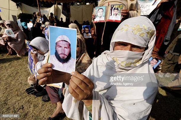 Pakistani woman holds a picture of her relative during a sitin protest in a camp set up by families of missing people at D Square outside the...