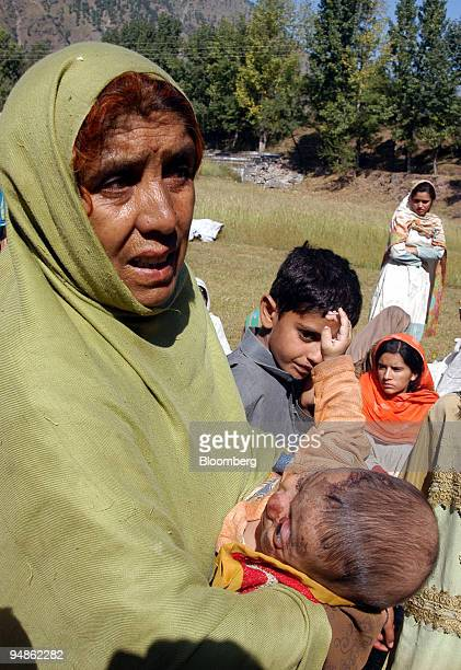 Pakistani woman holds an injured infant as her family waits for medical assistance to reach them in the quake devastated town of Balakot in the north...