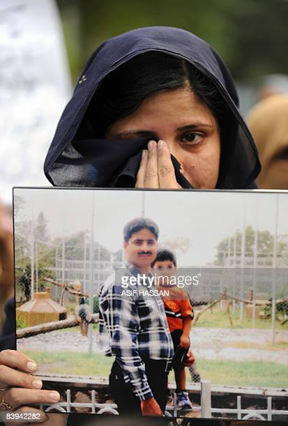 A Pakistani woman holds picture of her missing husband as she weeps during a protest of missing persons families in Karachi on December 7 2008 ahead...