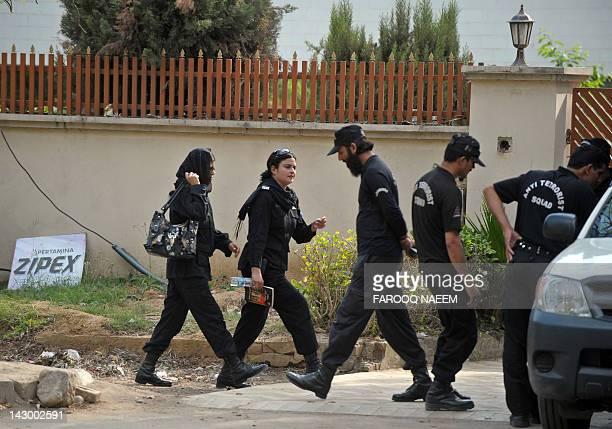 Pakistani woman police commandos and male colleagues change shifts outside the house where family members of slain AlQaeda chief Osama bin Laden are...