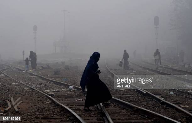 Pakistani woman walks through dense fog across railway tracks on the outskirts of Lahore on December 15 2017 / AFP PHOTO / ARIF ALI