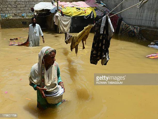 Pakistani woman walks through floodwaters following heavy monsoon rain in Karachi on August 5, 2013. Pakistani disaster relief officials issued fresh...