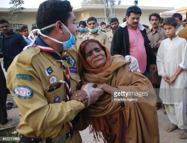 Pakistani woman whose relatives were killed is being comforted by scouts a day after it was hit a suicide attack at the 13th century old shrine of a...