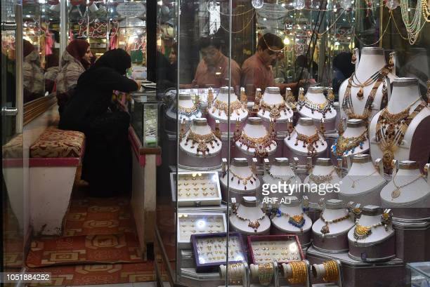 Pakistani women check gold jewellery at a shop in Lahore on October 11 2018
