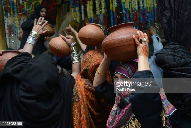 Pakistani women devotees bringing water for ablution of the graves at the shrine of the mausoleum of Ruqayyah Bint Ali known as Bibi Pak Daman in...