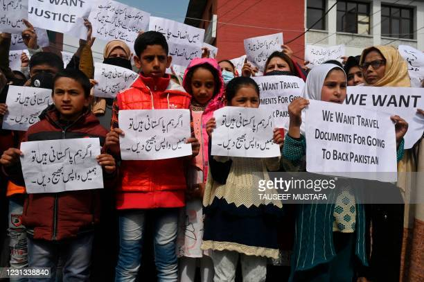 Pakistani women married to former Kashmiri militants and children hold placards during a protest urging Indian and Pakistani Prime Ministers to...