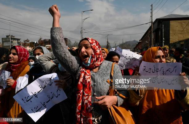 Pakistani women married to former Kashmiri militants shout slogans and hold placards during a protest urging Indian and Pakistani Prime Ministers to...