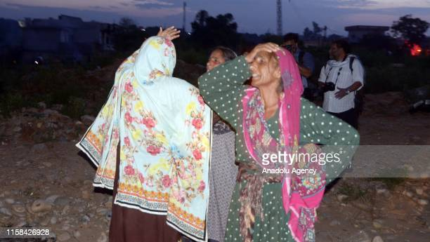 Pakistani women mourn over the daths od their loved ones at the site of a plane crash an Rawalpindi, Pakistan on July 30, 2019. Fifteen people were...