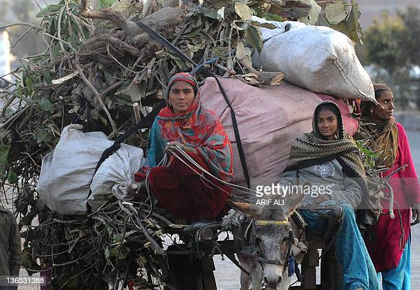 Pakistani women ride a donkey cart loaded with firewood in Lahore on January 7 2012 The government has hiked the national gas price by 14 percent...