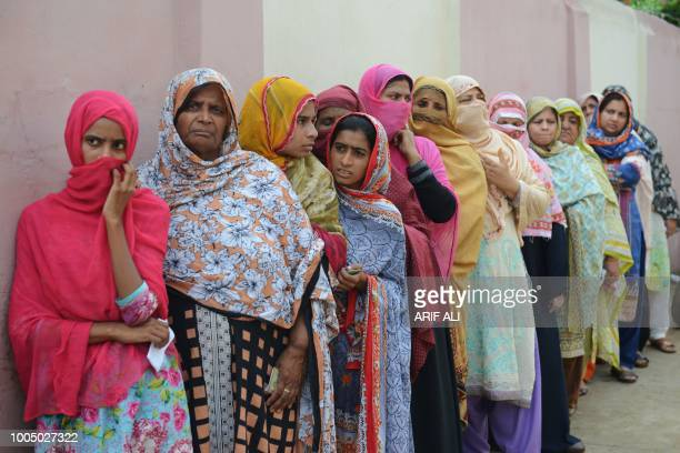 TOPSHOT Pakistani women stand in a queue as they wait to cast their vote outside a polling station during general election in Lahore on July 25 2018...