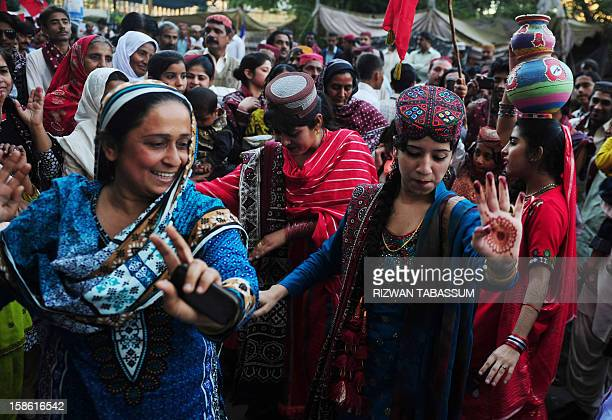 Pakistani women wearing traditional Sindhi cap and ajrak attire celebrate during a Sindh Cultural Day festival in Karachi on December 21 2012 The...
