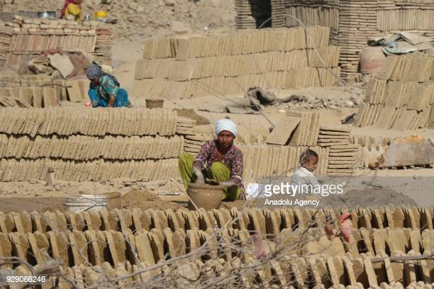 Pakistani women work to make bricks at a brick factory on the eve of International Women's Day in Karachi Pakistan on March 08 2018