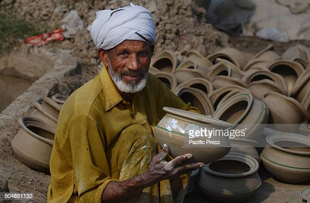 Pakistani worker busy in preparing clay to make different traditional clay pots Pottery is Pakistan's oldest handicraft Early men and women...