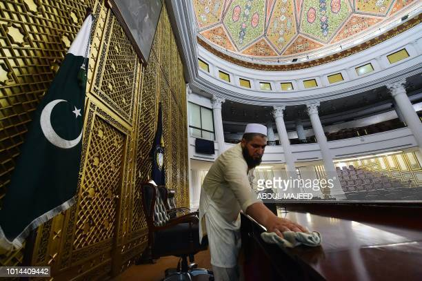Pakistani worker cleans the provincial assembly hall in Peshawar on August 10 ahead of the first session after the general election. - Pakistani...