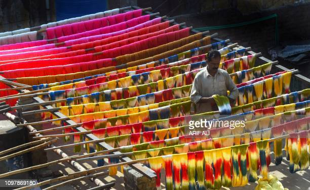 Pakistani worker dries fabric threads after dyeing them at a factory in Lahore on February 11 2019