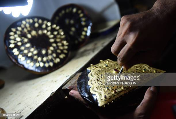 A Pakistani worker makes gold jewellery at a workshop in Karachi on October 10 2018 The International Monetary Fund said October 9 Pakistan has not...