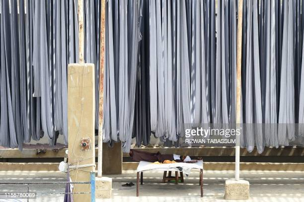 Pakistani worker rests under hanging cloths for dyeing at a garment factory in Karachi on July 15, 2019. - The International Monetary Fund approved a...