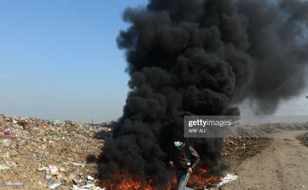 A Pakistani worker walks past dark smoke emitted from a fire as he monitors the work at a landfill site in Lahore on January 22, 2013. AFP PHOTO/Arif ALI