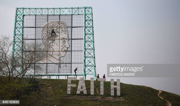 Pakistani workers arrange the image of country's founder Mohammad Ali Jinnah along a street in Islamabad on February 28, 2017 ahead of a multi-nation...