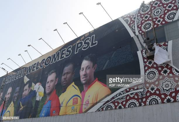 Pakistani workers fix a billboard featuring images of players ahead of the Pakistan Super League cricket match in Karachi on March 20 2018 Lahore...