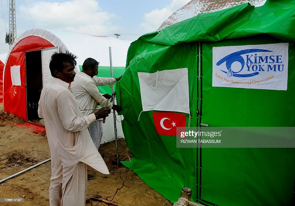 Pakistani workers fix a tent for flood a & Pakistani workers fix a tent for flood a Pictures | Getty Images