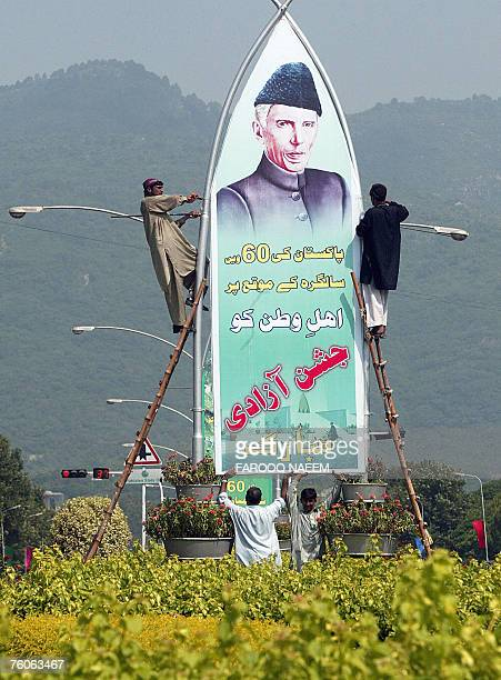 Pakistani workers install a banner featuring the founder of Pakistan, Mohammad Ali Jinnah on a street in Islamabad, 12 August 2007, in preparation...