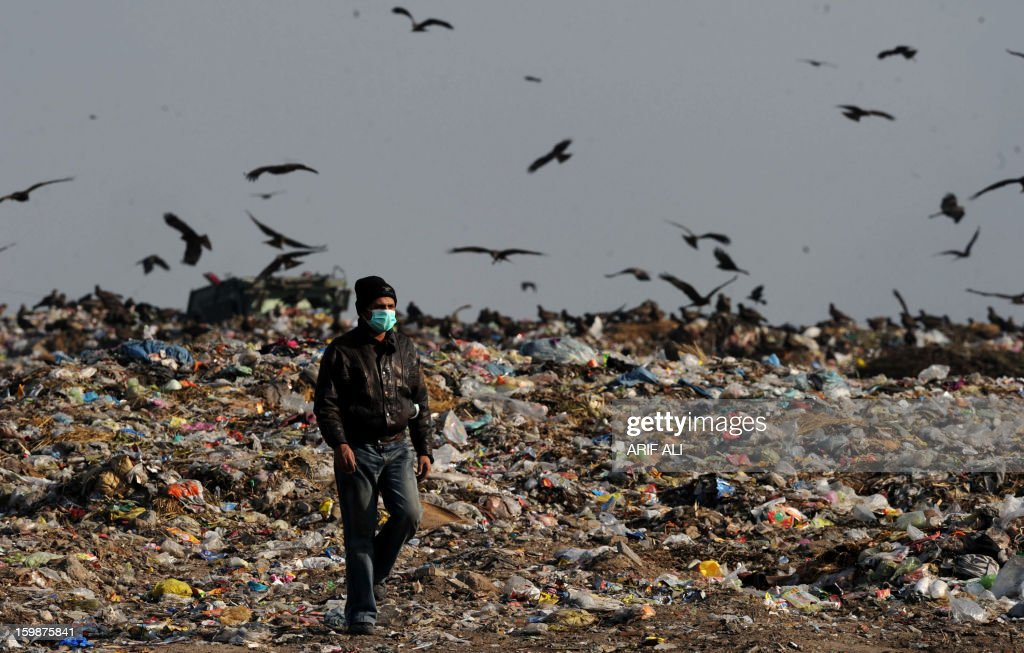 Pakistani workers monitor the work at a landfill site in Lahore on January 22, 2013. AFP PHOTO/Arif ALI